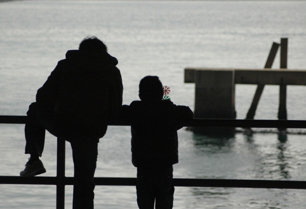 Black silhouette of father and son standing on a pier in front of gray water.