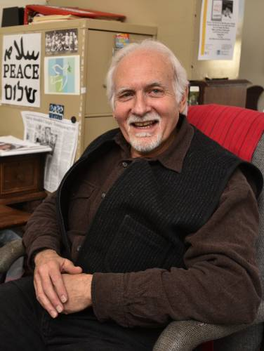 Man with white hair sitting in a chair and smiling at the camera. He is wearing a black vest over a brown shirt.