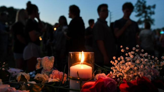 Foreground: candlelit flower memorial for Santa Fe high school. Students silhouetted in background.